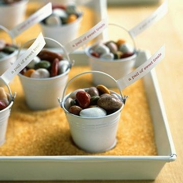 Wedding favor idea rock candy is mini pails on a tray filled with raw sugar for sand. Great idea for a beach theme wedding (and yummy!)