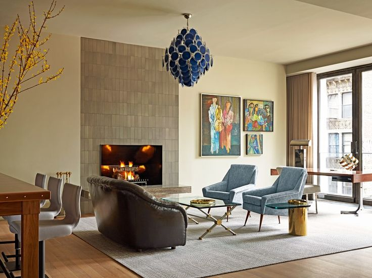 The wool Lepere rug defines the sitting room and is accented with two vintage Louis Paolozzi chairs from Lobel Modern and upholstered in a light blue de Le Cuona linen. The ceramic tile that surrounds the fireplace is from Heath Ceramics , and the vintage John Vesey X-base glass cocktail table is also from Lobel Modern.