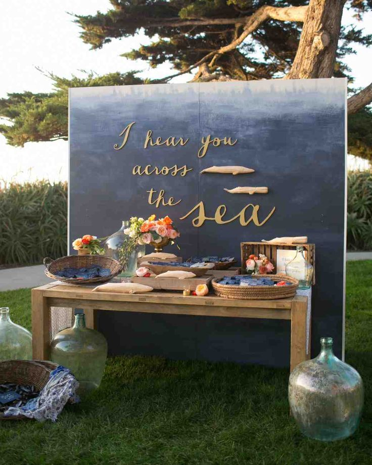 "11 Unique Ways to Show Off Your Favorite Quotes at Your Wedding | Martha Stewart Weddings - Feature the lyrics of your favorite song like this couple did—Jason Mraz's ""Lucky"" and its line ""I feel your whisper across the sea"" inspired a custom backdrop that was erected behind the escort cards. Painted to resemble the ocean, the setup was decorated with wooden whales to fit the nautical theme."