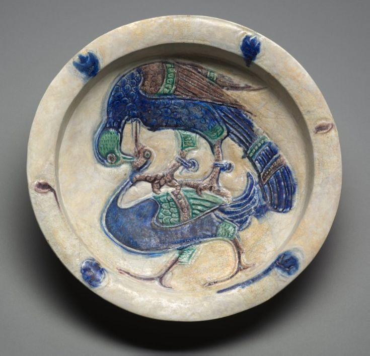 Dish with Falcon Attacking a Water Bird, 1100s Syria, possibly Tell Minis, Zangid or Ayyubid period fritware with carved decoration and underglaze-painted design (Lakabi ware),  H. 8.30 cm - D.  40.00 cm  Cleveland Museum of Art, 1938.7
