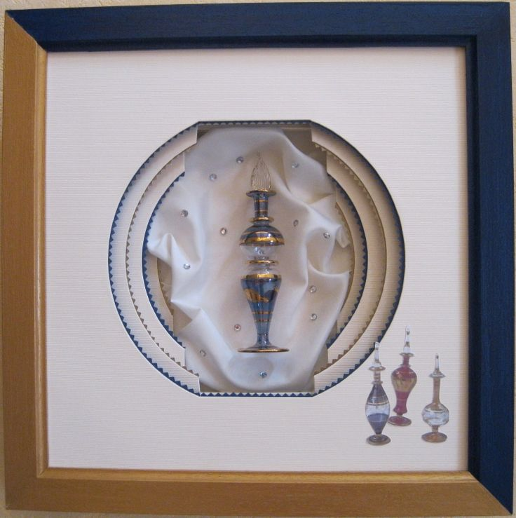 flacon de parfum (Installation) par Mad flacon de parfum , encadré dans une forme lampion, avec filets dentelés