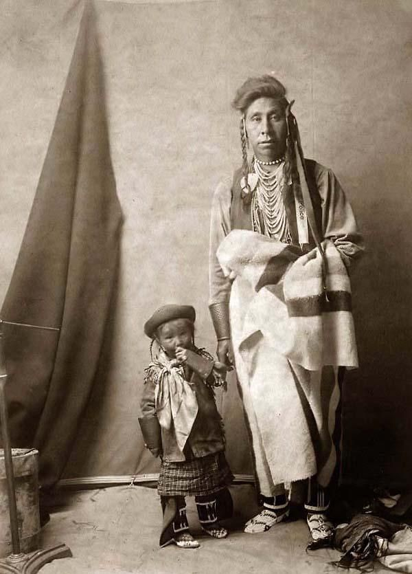Father and Son ~ Stunning image of Strong Enemy, a Crow Indian. It was taken in 1908 by Edward S. Curtis.    The image shows a Full-length portrait of a Crow Father and his child.