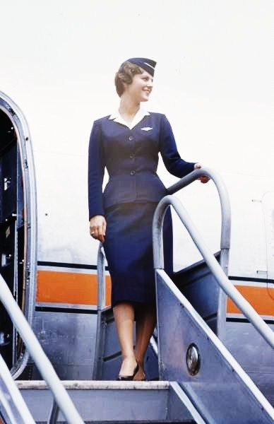 An airline stewardess posing next to a commercial airplane. Photograph by Peter Stackpole, 1950s.