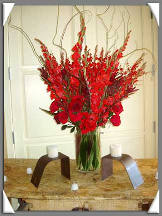 Wedding Flower Arrangement with Bright Red and Deep Red Gladiolus, Red Roses and Curly Willow. Ti leaves line the vase.