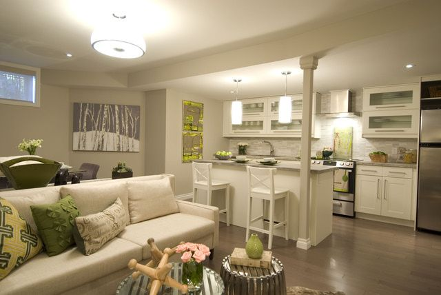 Despite the small windows this basement is airy and bright. Light walls, white cabinets and a white sofa keep the space light, while hits of silver and green add life and depth. Basement Apartments from HGTV's Income Property