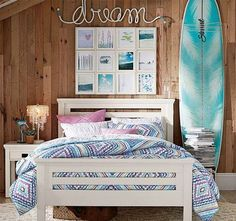 Beach themed bedroom with natural wooden wall and colorful patterned bedding.