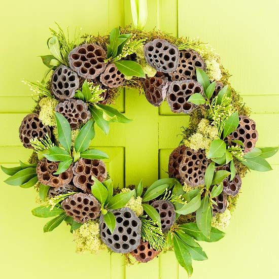 Lotus Pod Wreath:   Dried lotus pods become fun holiday baubles on this natural Christmas wreath. Hot-glue moss to a 9-inch wreath form, covering it completely, then add lotus pods in a random pattern to the wreath. Finish by adhering fresh or faux leaves and arborvitae sprigs to the moss around the lotus pods.