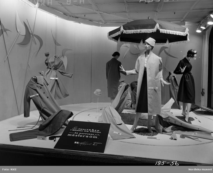 Skyltfönster på Nordiska Kompaniet 1956. Skyltdockor i damkappor från Mästersöm. Parasoll och en matta som dekor.