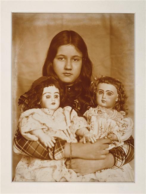 Denise assise de face, avec deux poupées serrées dans les bras Zola Emile