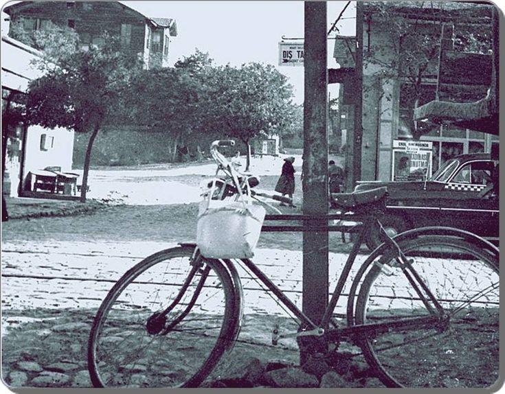 bir sokak, bir bisiklet ve arkada hayal meyal okunan bir sinema filmi afişi: ''Kadın Asla Unutmaz'' (1960,#Kadıköy)