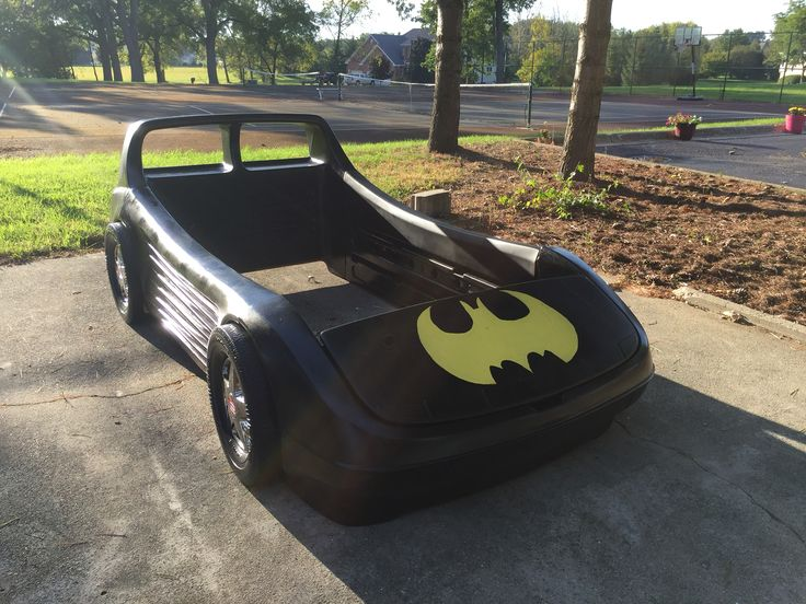 Batmobile Twin Bed Frame, which started out as a red, Little Tykes race car bed frame that I purchased second hand and up-cycled by spray painting with Rustoleum Black (four coats), and then hand painted with Glidden custom yellow to match my youngest son's Batman rug (Home Depot mixed up the color for me). I made a Batman logo stencil with a piece of thin poster board and drew it on with pencil prior to painting. The entire bed frame is coated with Polyurethane spray.