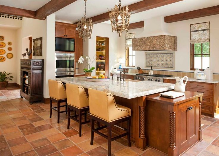 Southwestern charm fills this family-friendly kitchen. Terracotta tiles ground the space, while exposed wood beams add a rustic note above. The large kitchen island doubles as a dining spot and prep area, and elaborate light fixtures bring Old World style to the room.