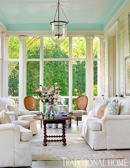 Cream sofa and chairs set a relaxed mood in this glassed-in porch. The ceiling is painted 'Bird's Egg' by Benjamin Moore.