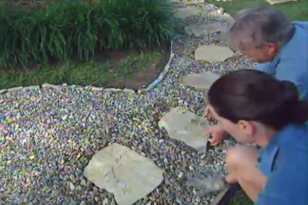Learn how to create a crushed rock pathway; includes details on layout, removing sod, landscape cloth, and installing flagstones.