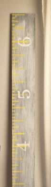 Growth chart ruler- Whitewashed gray growth chart ruler with yellow accents and white horizontal numbers