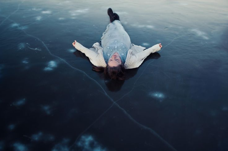 "It's been below freezing here all week, so I've been taking advantage of it while it lasts.  We found this huge frozen lake in the mountains and spent an afternoon slipping and sliding to our heart's content!  I found lots of cool fissures in the ice, and my sister graciously lay down on the freezing surface to pose for me (...I may have begged for a while first).  There is something absolutely magical about winter!  We also went to see the movie ""Frozen"" after this shoot.  It was adorable…"