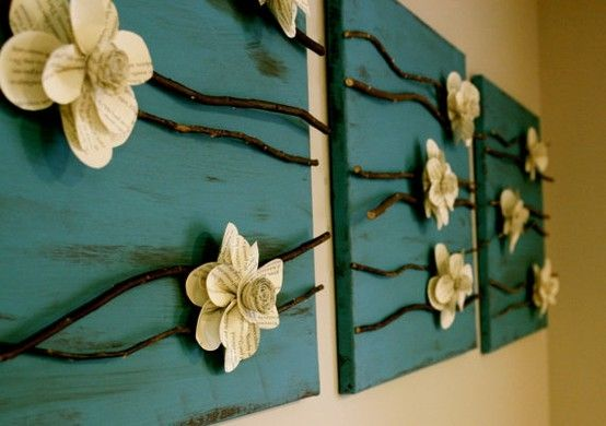 Paper flowers and branches on a canvas.