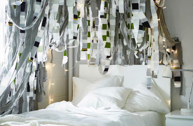 Stoffstreifen hängen über einem Bett herab.