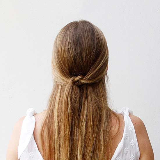 Do you know how to tie a knot? Then you can accomplish this super simple half updo. Take sections of hair from each side of your face, knot together twice, and secure with pins.  Get Step-by-Step Instructions
