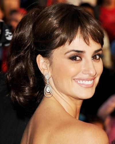 "Everyday ponytail with a vintage twist-literally! ""Penelope Cruz created fullness by twisting the length of her ponytail around to make it shorter,"" ""The clip-on bangs were a fun, retro-inspired addition to her signature style."" EXPERT TIP: Recreating this style works best with longer hair. ""Spiral hair upward as if you are pulling it into a French Twist."" The ponytail is formed from the loose, upswept ends of the twist. ""Large hair pins have more holding power, so they'll work best."