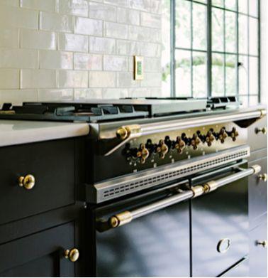 White Counters, White Backsplash, Black Oven, Black Cabinets & Brass details