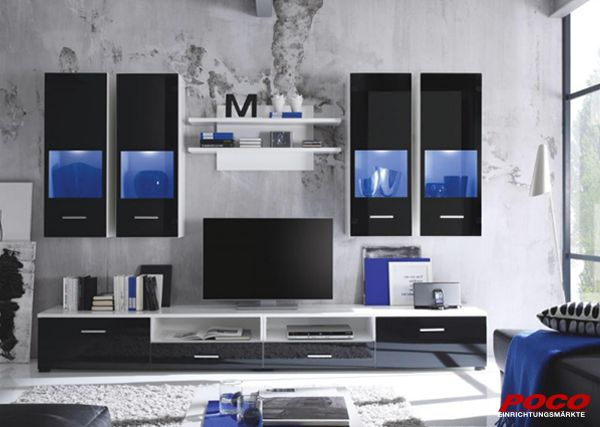 Diese Wohnwand besticht durch Ihre schlichte Eleganz. Die schwarzen Glasfronten der Hängevitrinen werden gekonnt in Szene gesetzt, durch die blaue LED Spot Beleuchtung. Diese ist im Lieferumfang ebenfalls enthalten. Im geräumigen TV-Lowboard haben Ihre TV- und Hifi Geräte einen besonderen Platz.