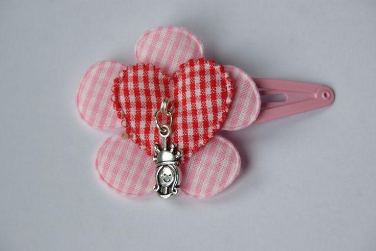 Leuke knip 5 cm met een geruite roze bloem met daarbovenop een rood geruit hart met bedel. Door een nieuw systeem is het knipje zo te draaien dat het steeds mooi in de haren zit aan welke kant je de knip ook draagt.  www.lotenlynn.nl https://www.facebook.com/lotenlynnlifestyle