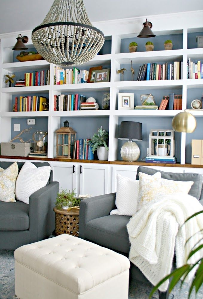 Check out the sky blue back painting on these white bookcases!  That looks fantastically spacious and classy, while not being at all fussy. -   DIY built in bookcases with kitchen cabinets from thriftydecorchick