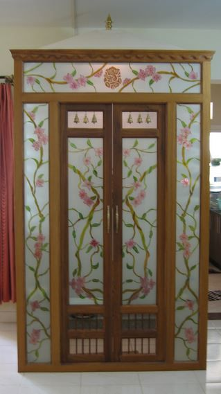 Get these pooja room designs in glass for living room or hall. Pooja room designs in glass are transparent thus allow you to view your deities from outside.