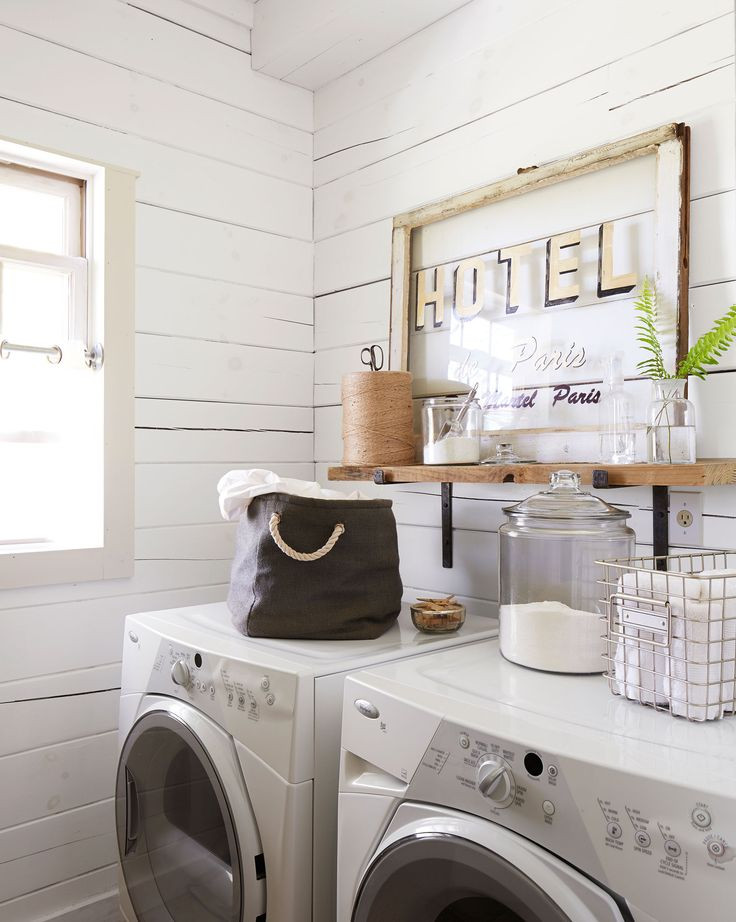 A vintage hotel sign, along with glass canisters for detergent and such, prettifies the laundry room. The walls are painted Simply White by Benjamin Moore. - CountryLiving.com
