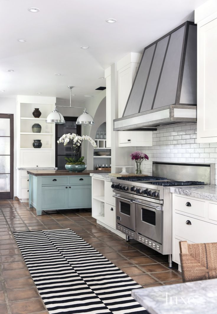 A fresh shade of mint green brings color to the island in this mostly white kitchen; a Viking range is topped with a hood White customized. Tile from Waterworks covers the backsplash, and pendants from Restoration Hardware provide a touch of simplicity. #LuxeTurns10