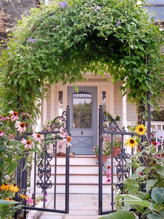 Love this vine-covered arbor and wrought iron gates and front door ?