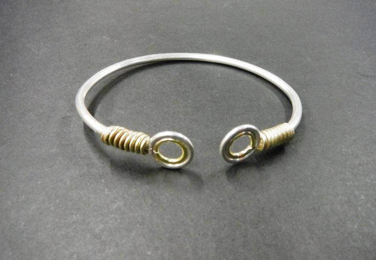 Recycled gold onto the ends of this clever contemporary open bangle/cuff by Paul Bradley
