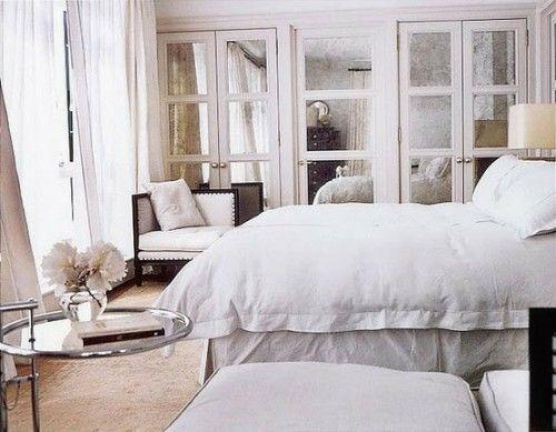 Antiqued mirrored closet doors to enlarge look of small bedroom