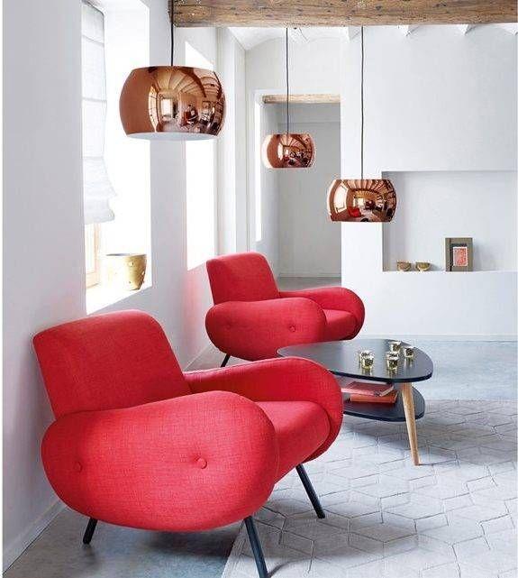 Dans ce loft blanc la couleur est amenée par une lampe suspendue boule ronde en cuivre et un fauteuil rouge style futuriste années 60 qui a été remis a neuf en suivant les conseils comment retapisser un fauteuil soi-meme