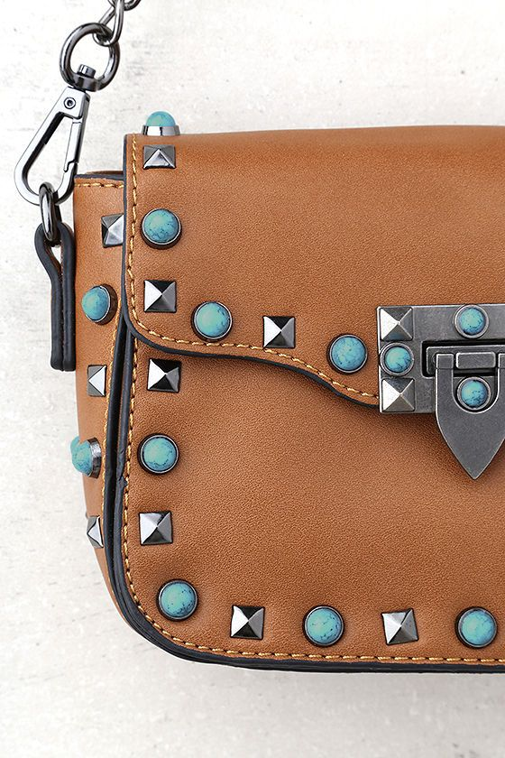 Carry those essential festival treasures in the Taos Brown Studded Purse! Supple vegan leather shapes this flat bottom design purse with gunmetal studs and turquoise stone trim.