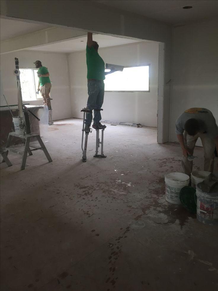 Taping the drywall, men on stilts!