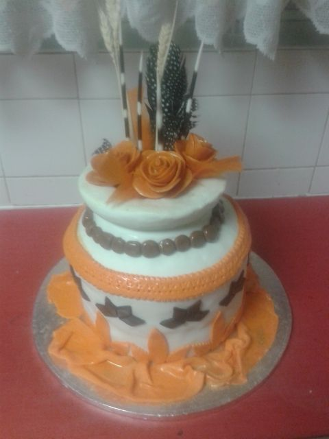 African Wedding Cake by Fairyfield Cakes 0839427354. 5 Layer cake covered wit fondant icing. Decore made from fondant except quills and feathers. Roses made by hand out of Fairyfield Moulding chocolate.