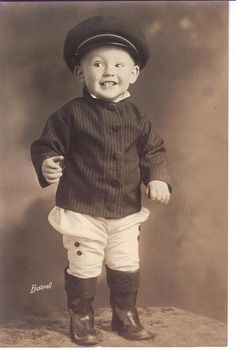 An old picture of a boy dressed in typical 1940s clothes .