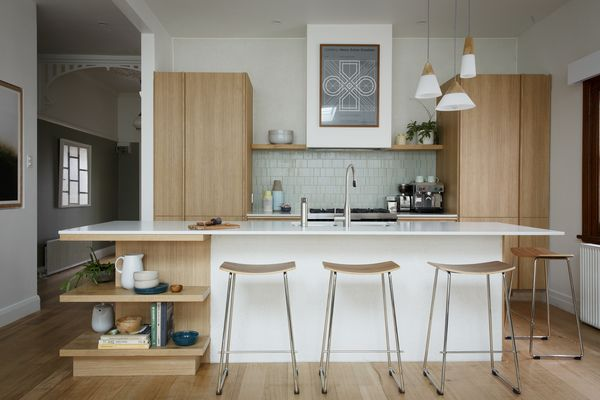 MODERN MID-CENTURY: The strong sense of timber-grain cabinetry is bang on brief and accentuated by the seamless integration of the appliances. This is a high-end look that is functional and stunning in its simplicity. Featuring:  •	Cabinetry Impressions Sublime Teak Riven  •	Caeasarstone® benchtops in Fresh Concrete with 20mm edge & Pale Lancelot Oak Streamline with 38mm edge (Island Display Shelving)  •	Pull Out Pantry  •	Hettich ArciTech Drawer System with Glass Design Sides