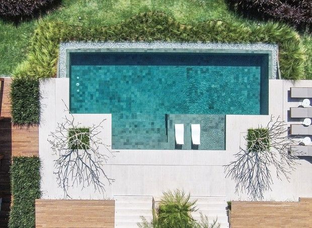 De cima, é possível admirar o desenho criado com duas variações de capim-do- texas: o verde foi plantado rente à piscina e o rubro, nas margens do terreno. Entre eles, grama-esmeralda (Foto: Iuri Seródio/Divulgação)
