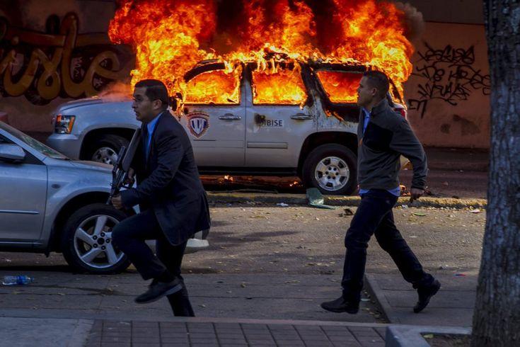 Miembros de la CICPC caminan frente a un vehículo incendiado durante una marcha convocada por la oposición, en Caracas (Venezuela). MIGUEL GUTIÉRREZ (EFE)