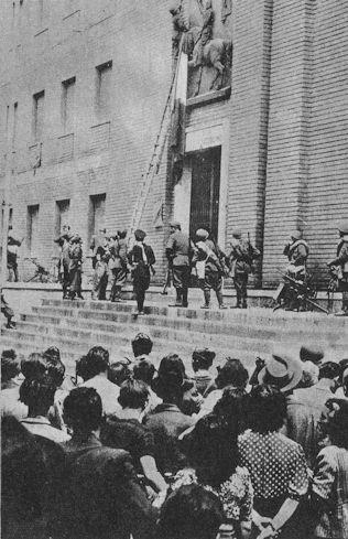 Soldats italiens recouvrant les emblèmes du fascisme par un drapeau italien à Milan