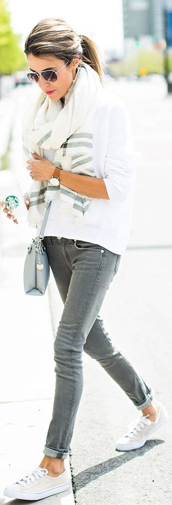 Christine Andrew is wearing a white linen sweater from J Brand, white and grey scarf from Ily Couture, grey skinny high rise jeans from Rag & Bone, bag from Skagen and the sneaker are from Keds