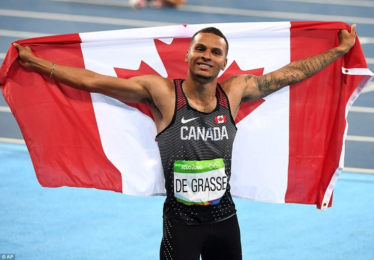 Canada's Andre de Grasse flies the flag as he celebrates his bronze medal in the…