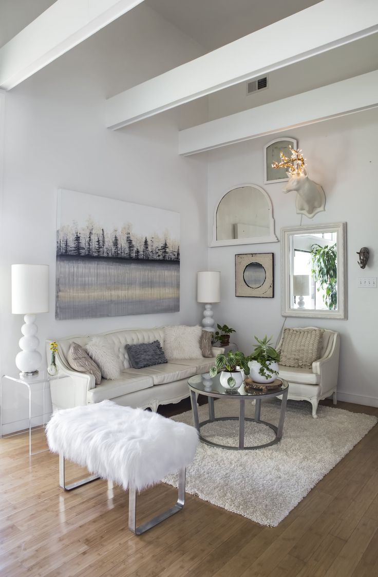"""The living room's light color palette and the open concept design add to the bright, airy feeling in the home. """"Adding a round piece of furniture is a design trick of mine. I think it gives the space a softness/sexiness,"""" Tami says about her coffee table, which she sourced from a sale of items used on HBO's television show Treme."""