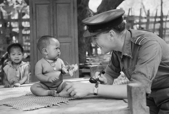 Squadron Leader Joseph Heaven an RAF Methodist Chaplain from Bedford playing with a Burmese baby in a village near Monywa where he found forty Burmese Christians who had been evacuated from the Methodist Mission Compound and School at Monywa. It was there that he held the first Methodist service in that part of Burma for three years March 1945.