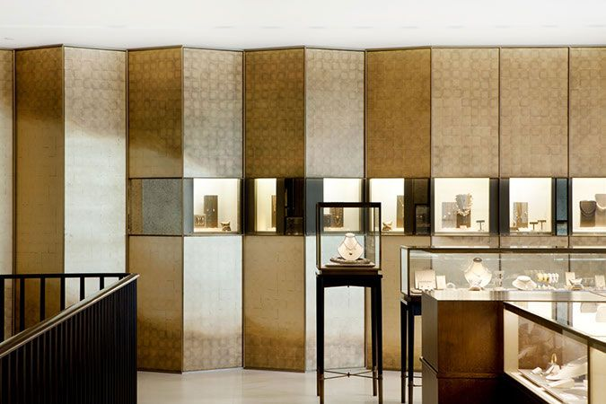 A translucent and textured glass wall with vertical bands of patinaed bronze, is a striking design element in the Shanghai Tiffany & Co. store. Here,   the horizontal band contains glass vitrines, for displaying their elegant product.