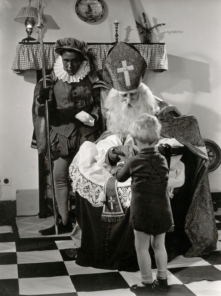 Een klein jongetje krijgt een speculaaspop van Sinterklaas. Sint zit voor een schouw met een geruit 'valletje'(gordijntje). Piet heeft de staf in zijn ene hand en een pakje in de andere. Zonder plaats,1952