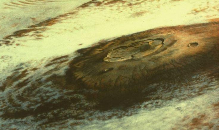 Le sommet du volcan Olympus Mons émerge d'une véritable mer de nuages de cristaux de glace d'eau... la scène a été photographiée par la sonde Viking 1 à une distance de 8000 km. Le sommet de la couche de nuages est situé à 19 kilomètres au dessus du sol et sous 8 kilomètres du sommet du volcan.